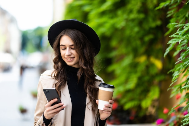 Vrolijke jonge vrouw met een papieren beker, surfende telefoon in de straat