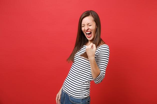 Vrolijke jonge vrouw met gesloten ogen in gestreepte kleding die vuist balt als winnaar en schreeuwt