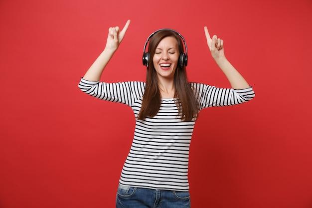Vrolijke jonge vrouw met gesloten ogen met draadloze koptelefoon dansen, muziek luisteren, wijzende vingers omhoog geïsoleerd op rode achtergrond. mensen oprechte emoties, lifestyle concept. bespotten kopie ruimte.