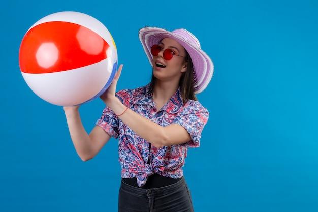 Vrolijke jonge vrouw met hoed die rode zonnebril draagt die opblaasbare bal werpt die met gelukkig gezicht glimlacht dat zich op blauw bevindt