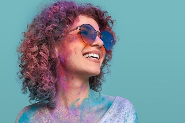 Vrolijke jonge vrouw met holi-kleuren op huid