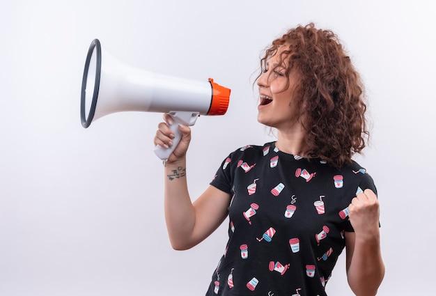 Vrolijke jonge vrouw met kort krullend haar schreeuwen naar megafoon verlaten en gelukkig