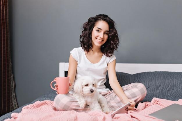 Vrolijke jonge vrouw met krullend donkerbruin haar in pyjama's koelen op bed met hondje in modern appartement. mooi model thuis ontspannen met een kopje koffie, chatten op de telefoon, glimlachend