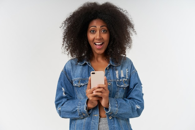 Vrolijke jonge vrouw met krullende donkere huid die mobiele telefoon in handen houdt en er een foto mee maakt, breed glimlachend terwijl ze in vrijetijdskleding over een witte muur poseert