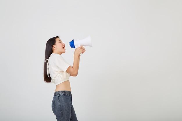 Vrolijke jonge vrouw met megafoonaankondiging in geïsoleerde studio