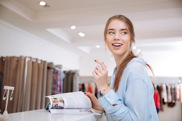 Vrolijke jonge vrouw met mode-tijdschrift staan en lachen in kledingwinkel
