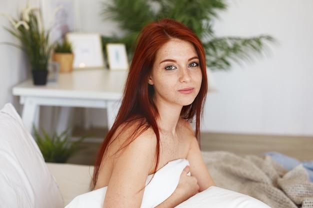 Vrolijke jonge vrouw met rood haar, sproeten en naakte schouders zittend op bed, gewikkeld in een deken, gelukkig gevoel, wakker in hotelkamer op eerste dag van huwelijksreis, charmant glimlachend