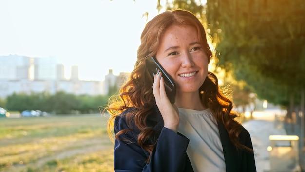 Vrolijke jonge vrouw met sproeten en rood golvend haar praat op hedendaagse mobiele telefoon in groen stadspark bij zonsondergang licht dichtbij zicht