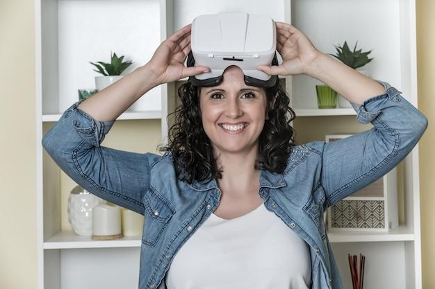 Vrolijke jonge vrouw met virtual reality bril in lichte hedendaagse kantoor