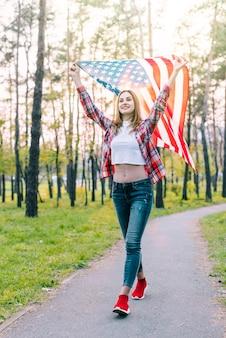Vrolijke jonge vrouw met vlag van de vs