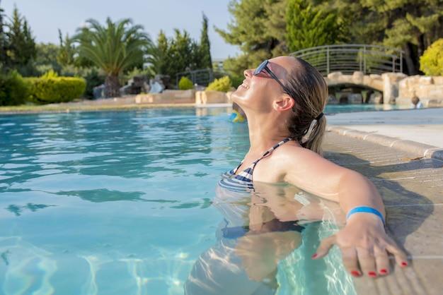 Vrolijke jonge vrouw met zonnebril in een zwembad onder het zonlicht overdag