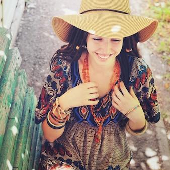 Vrolijke jonge vrouw portret met dreadlocks gekleed in boho stijl jurk en ketting, zonnige buiten