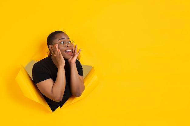 Vrolijke jonge vrouw poseert in een gescheurde gele papieren gatmuur, emotioneel en expressief schreeuwend met luidspreker