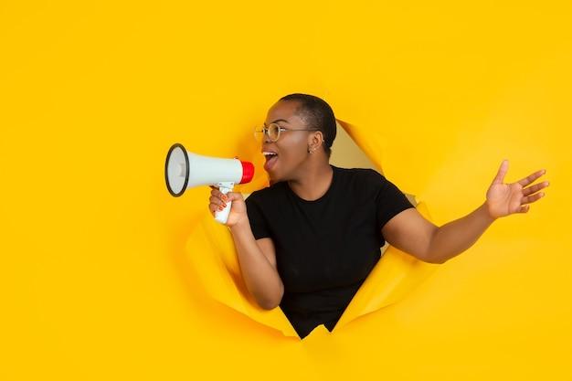 Vrolijke jonge vrouw poseert in gescheurde gele papieren gatenmuur, emotioneel en expressief schreeuwend en bellend met spreker