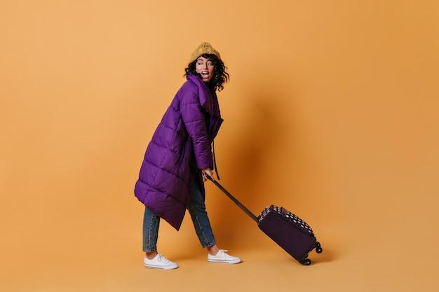 Vrolijke jonge vrouw poseren met koffer