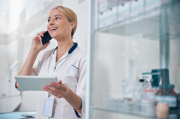 Vrolijke jonge vrouw praat op smartphone terwijl ze tablet vasthoudt tijdens de werkdag in de kliniek