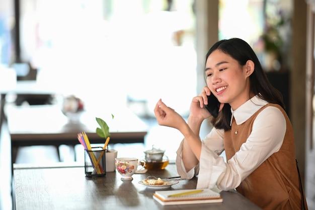 Vrolijke jonge vrouw praten op mobiele telefoon tijdens het aanbrengen in moderne coffeeshop