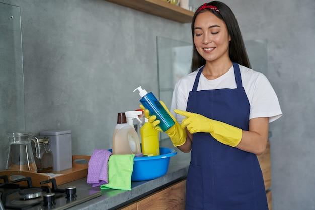 Vrolijke jonge vrouw, schoonmaakster die beschermende handschoenen draagt, glimlachend en huishoudelijk schoonmaakmiddel vasthoudt terwijl ze zich klaarmaakt om het huis schoon te maken. schoonmaak, schoonmaak dienstverleningsconcept