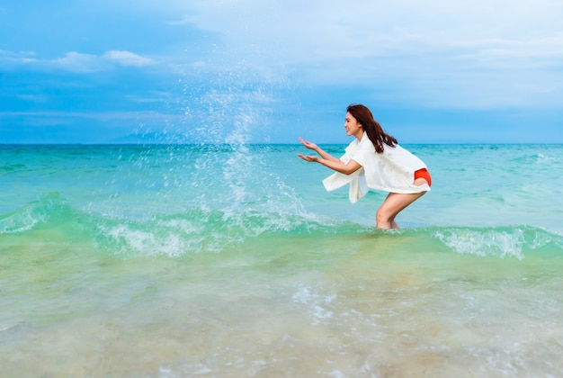 Vrolijke jonge vrouw spelen water plons in het zee strand op koh munnork island, rayong, thailand