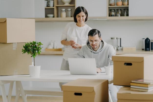 Vrolijke jonge vrouw staat achter haar man die op laptopcomputer werkt, poseren in moderne keuken van hun nieuwe appartement, omringd met kartonnen dozen, nadenken over modern design