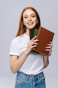 Vrolijke jonge vrouw student boek houden en kijken naar camera op geïsoleerde achtergrond