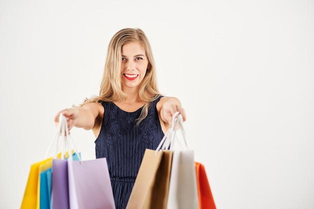 Vrolijke jonge vrouw uitgestrekte handen met boodschappentassen, geïsoleerd op wit