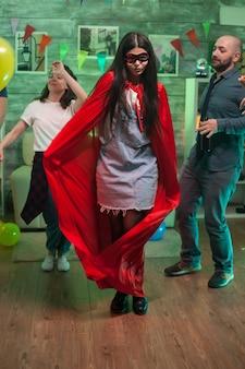 Vrolijke jonge vrouw verkleed als een superheld op vriendenfeestje.