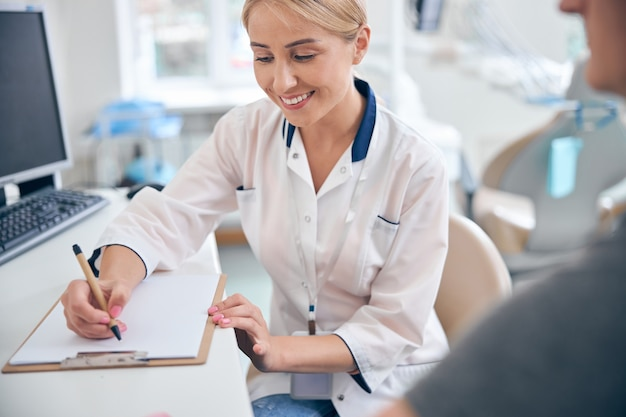 Vrolijke jonge vrouw zit aan bureau met computer en maakt aantekeningen terwijl ze naar mannelijke patiënt luistert