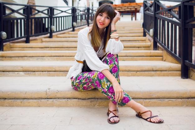 Vrolijke jonge vrouw zittend op de trap, stijlvolle zomer lichte outfit, trendy kapsel. vakantiestemming. tropische print. vers close-up portret.