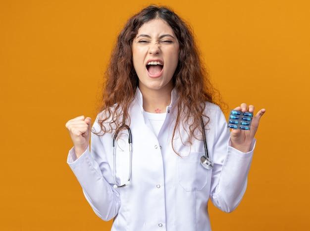 Vrolijke jonge vrouwelijke arts die een medisch gewaad en een stethoscoop draagt die een pakje medische capsules toont aan de camera die naar de voorkant kijkt en ja gebaar doet geïsoleerd op een oranje muur