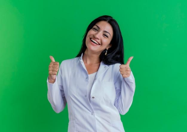 Vrolijke jonge vrouwelijke arts die medische mantel draagt die duimen toont die omhoog op groene muur met exemplaarruimte worden geïsoleerd