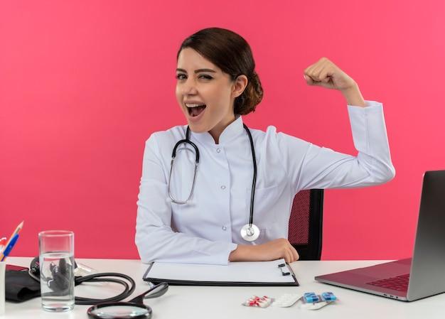 Vrolijke jonge vrouwelijke arts die medische mantel draagt met een stethoscoop zittend aan een bureau werkt op de computer met medische hulpmiddelen doet sterk gebaar op geïsoleerde roze muur met kopie ruimte