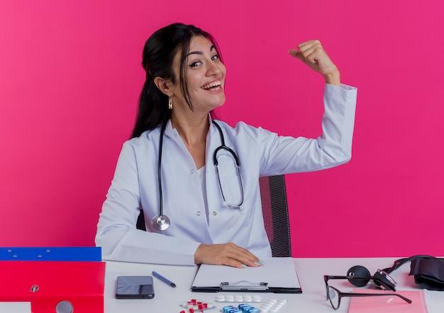 Vrolijke jonge vrouwelijke arts die medische mantel en stethoscoop draagt ?? die aan bureau zit met medische hulpmiddelen die hand op bureau zetten die sterk gebaar doen dat op roze muur wordt geïsoleerd