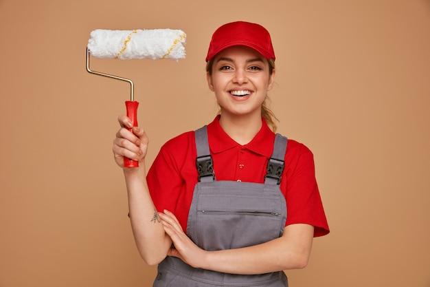 Vrolijke jonge vrouwelijke bouwvakker die glb en de eenvormige rol van de holdingsverf draagt die hand op wapen houdt