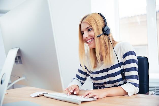 Vrolijke jonge vrouwelijke exploitant met hoofdtelefoon