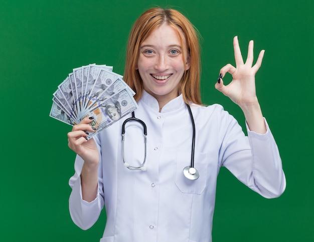 Vrolijke jonge vrouwelijke gemberdokter met een medisch gewaad en een stethoscoop die geld vasthoudt en een goed teken doet dat op een groene muur is geïsoleerd