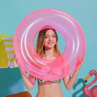 Vrolijke jonge vrouwelijke holdings drijvende cirkel in studio