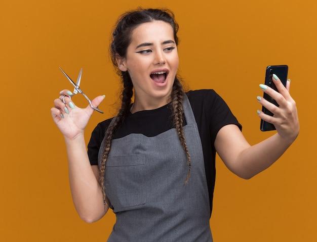 Vrolijke jonge vrouwelijke kapper in eenvormige schaar houden en kijken naar telefoon in haar hand geïsoleerd op oranje muur