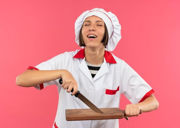 Vrolijke jonge vrouwelijke kok in chef-kok het uniforme mes en snijplank met gesloten ogen geïsoleerd op roze