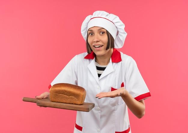 Vrolijke jonge vrouwelijke kok in chef-kok uniform bedrijf en wijzend met de hand op snijplank met brood erop geïsoleerd op roze