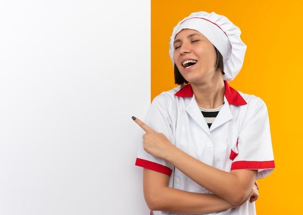 Vrolijke jonge vrouwelijke kok in eenvormige chef-kok die zich voor witte muur bevindt en ernaar richt met gesloten ogen die op sinaasappel worden geïsoleerd