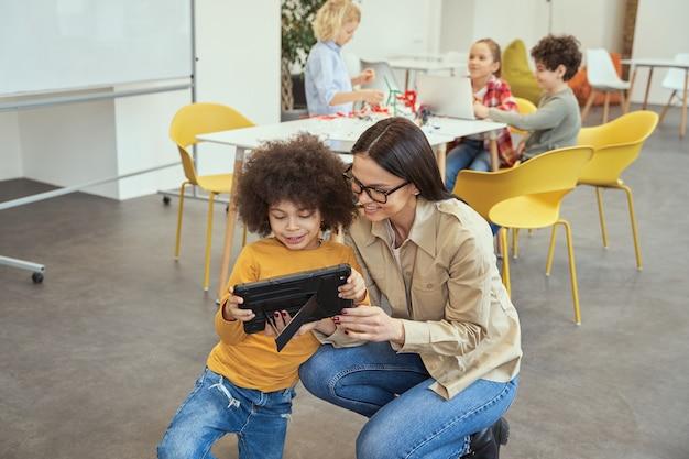 Vrolijke jonge vrouwelijke leraar in vrijetijdskleding glimlachend tijdens het kijken naar video op tablet pc samen met