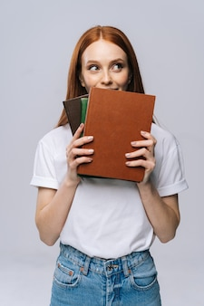 Vrolijke jonge vrouwelijke student die boeken vasthoudt en wegkijkt op geïsoleerde achtergrond