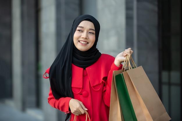 Vrolijke jonge vrouwen die boodschappentas houden bij buiten.