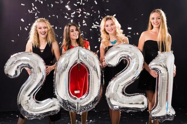 Vrolijke jonge vrouwen die oudejaarsavond vieren