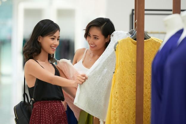 Vrolijke jonge vrouwen die voor kleding winkelen