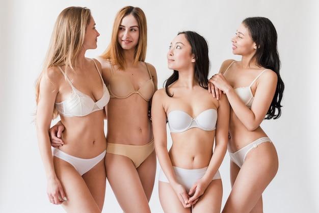 Vrolijke jonge vrouwen in ondergoed die elkaar bekijken
