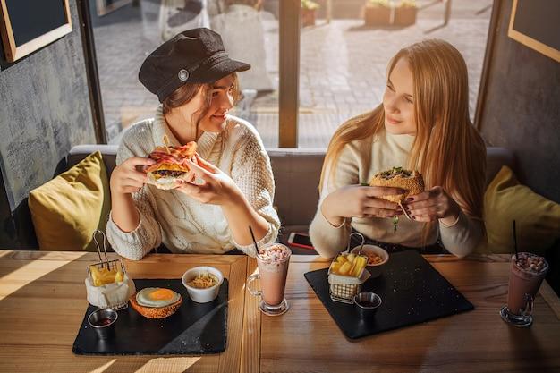 Vrolijke jonge vrouwen kijken naar eahc en glimlachen. ze zitten aan tafel in een café en houden hamburgers vast. jonge vrouwen zijn blij.