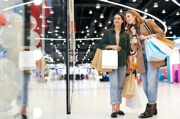 Vrolijke jonge vrouwen met boodschappentassen die zich bij vitrine bevinden en kleren in wandelgalerij kiezen