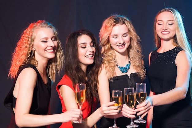 Vrolijke jonge vrouwen met glazen champagne op een feestje